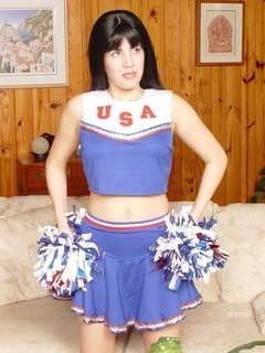 Sexy cheerleader posing with her pompoms and hikes up her skirt to show off her cute panties