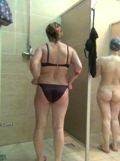 Two shy cuties take showers while still wearing their swimsuits